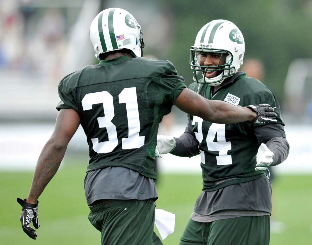 FILE - In this July 28, 2012, file photo, New York Jets cornerbacks Darrelle Revis (24) and Antonio Cromartie laugh at their NFL football training camp in Cortland, N.Y. The band is getting back together in the New York Jets' secondary. Cornerback Antonio Cromartie agreed to terms with the Jets on a four-year contract, worth $32 million in base salary, a person familiar with the deal told The Associated Press. The move Thursday, March 12, 2015, comes a day after New York finalized a deal to bring Darrelle Revis back on a five-year, $70 million deal. (AP Photo/Bill Kostroun, File) ORG XMIT: NY159
