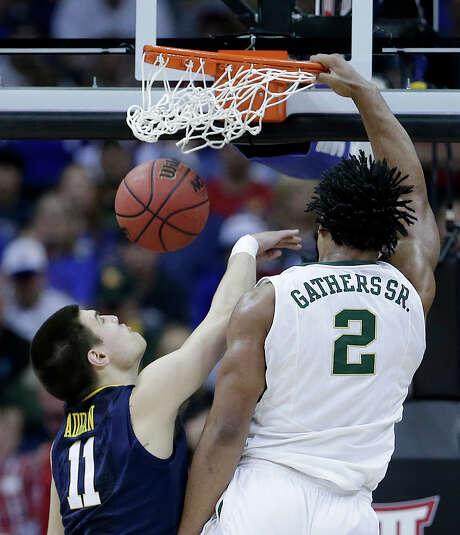 Baylor's Rico Gathers gets past West Virginia's Nathan Adrian to rattle the rim on a dunk in the second half of the Bears' 80-70 victory over the Mountaineers in the Big 12 tournament quarterfinals Thursday at Kansas City, Mo. Gathers finished with 14 points. Photo: Charlie Riedel, STF / AP