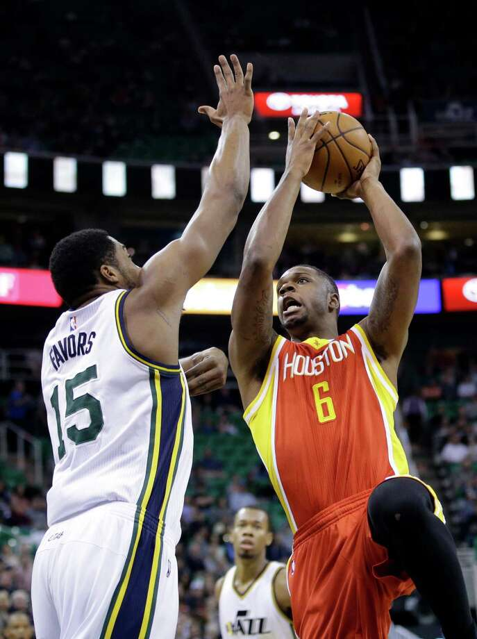 Rockets forward Terrence Jones, right, takes the ball strong to the basket against Jazz forward Derrick Favors. Photo: Rick Bowmer, STF / AP