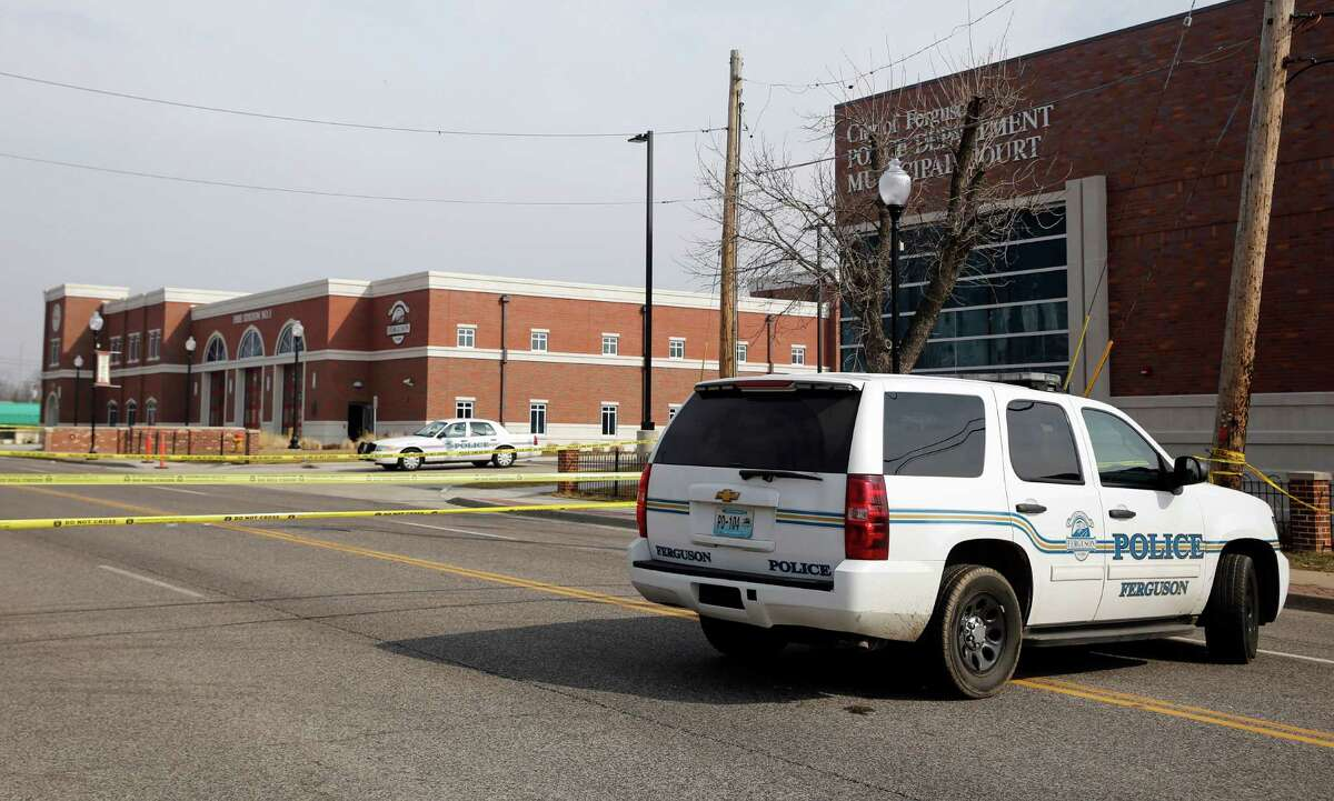 Police cars and crime scene tape block access to the Ferguson Police Department Thursday, March 12, 2015, in Ferguson, Mo. Two officers were shot in front of the police department early Thursday as demonstrators gathered after the police chief resigned in the wake of a scathing Justice Department report alleging bias in the police force and local courts. (AP Photo/Jeff Roberson) ORG XMIT: MOJR108