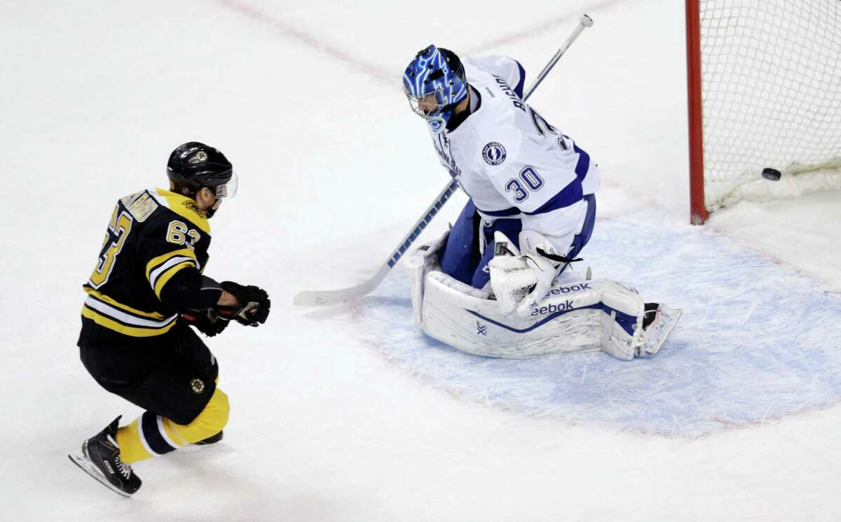 Boston Bruins left wing Brad Marchand (63) beats Tampa Bay Lightning goalie Ben Bishop (30) for the game-winning shot in a shootout during an NHL hockey game in Boston, Thursday, March 12, 2015. The Bruins defeated the Lightning 3-2. (AP Photo/Charles Krupa) ORG XMIT: MACK111
