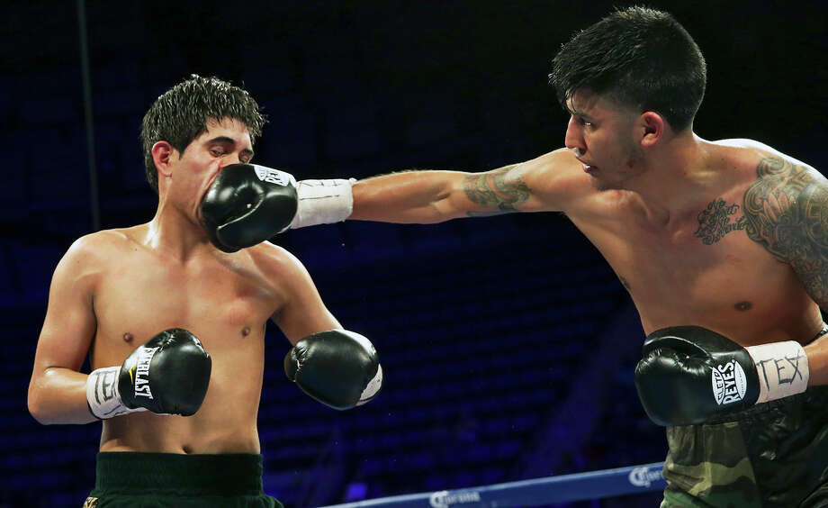 Armando Cardenas  (right) of San Antonio plugs a face shot as he defeats Marco Antonio Solis of Austin in a boxing undercard event at Freeman Coliseum on March 12, 2015. Photo: Tom Reel / San Antonio Express-News