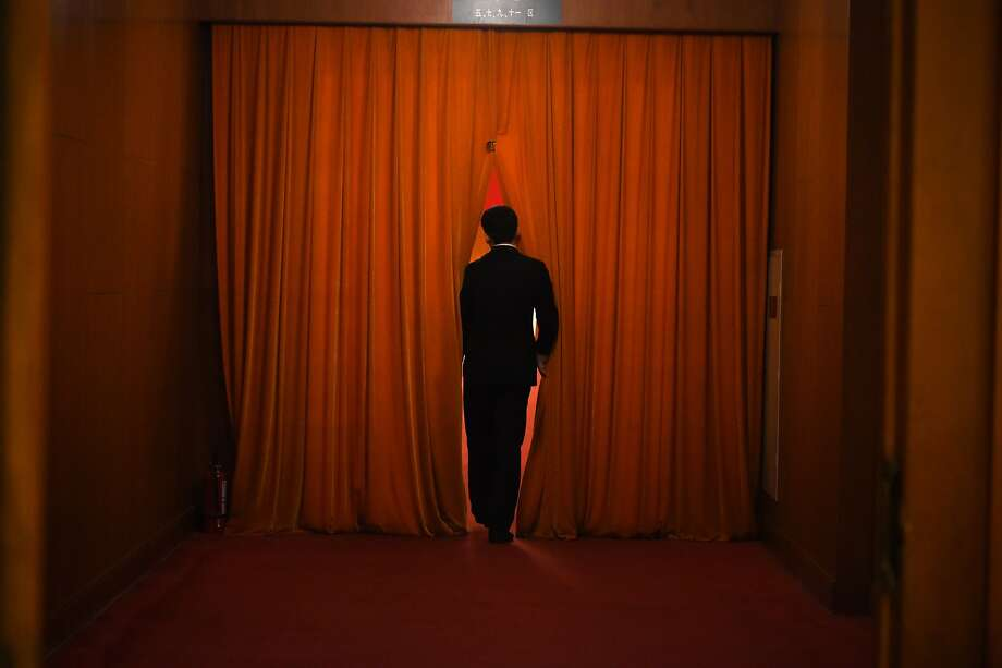 "A security guard watches through the curtain during the 3rd plenary session of the third session of the 12th National People's Congress at the Great Hall of the People in Beijing on March 12, 2015. China's Communist Party-controlled legislature, the National People's Congress (NPC), gathers in the capital for the annual show of political theater, with the ""rule of law"" high on the agenda. Photo: Wang Zhao, AFP / Getty Images"