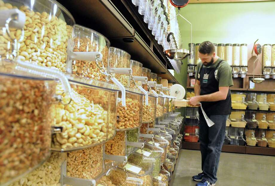John Stanton, of Houston 77007, puts the finishing touches on the bull food section at The Woodlands Whole Foods Market, 1925 Hughes Landing Boulevard, in The Woodlands. The store is opening on March 18th.  Photograph by David Hopper Photo: David Hopper, For The Chronicle / freelance