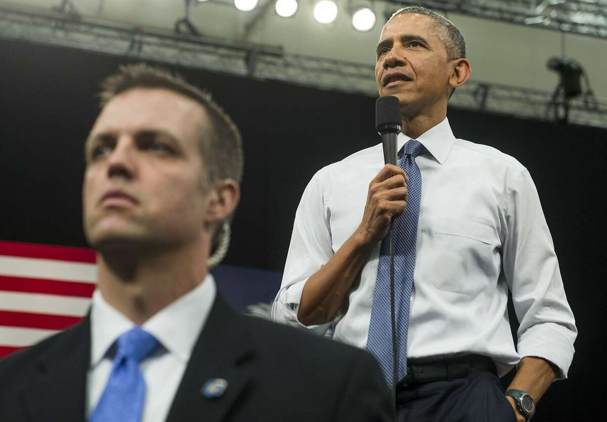 A Secret Service agent stands guard as US President Barack Obama answers questions during a town hall event at Benedict College in Columbia, South Carolina, March 6, 2015. AFP PHOTO / SAUL LOEBSAUL LOEB/AFP/Getty Images