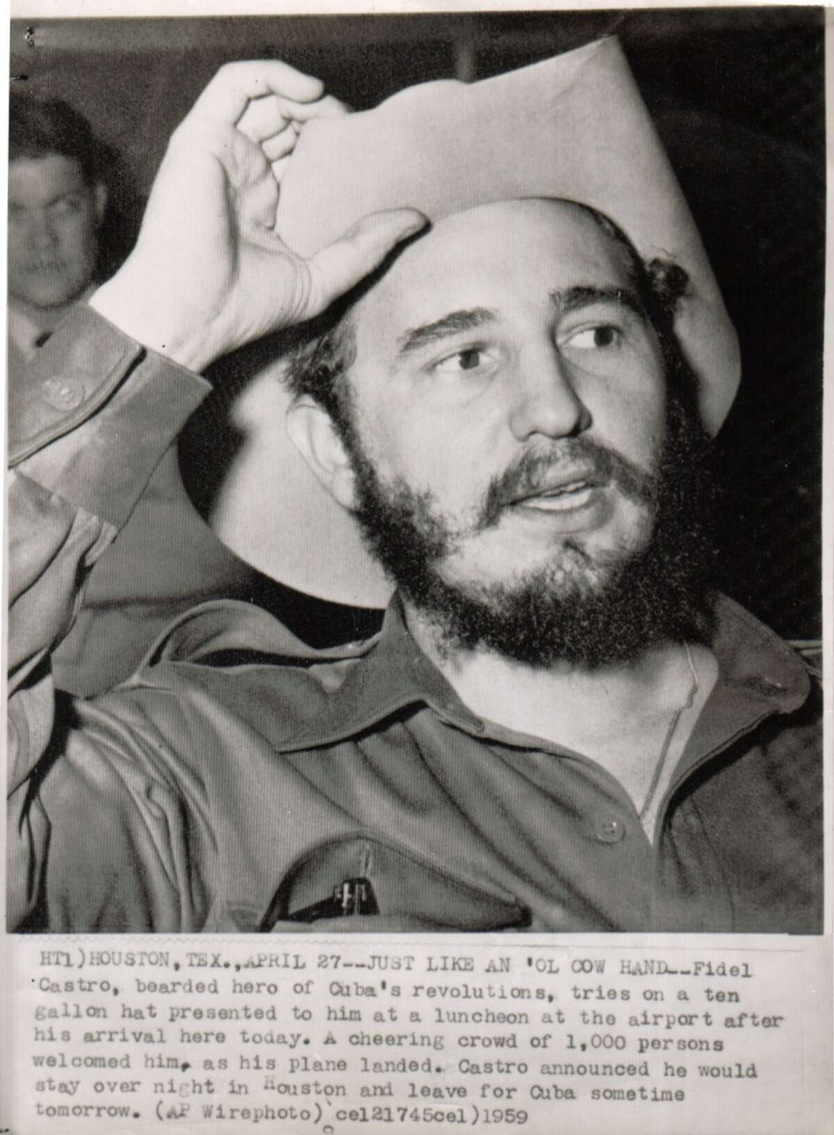 Fidel Castro, bearded hero of Cuba's revolutions, tries on a ten gallon hat presented to him at a luncheon at the airport after his arrival on April 27, 1959.