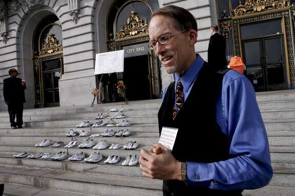 John Lowell, on Friday Nov. 7, 2014, who holds a seat on the Pedestrian Safety Advisory Committee, near the steps of City Hall where twenty eight pairs of shoes have been placed to represent the lives lost in 2014 to traffic related incidents. Members of San Francisco's Vision Zero Coalition gathered in San Francisco, Calif., to draw attention to the alarming increase of traffic related deaths on the streets of the city.