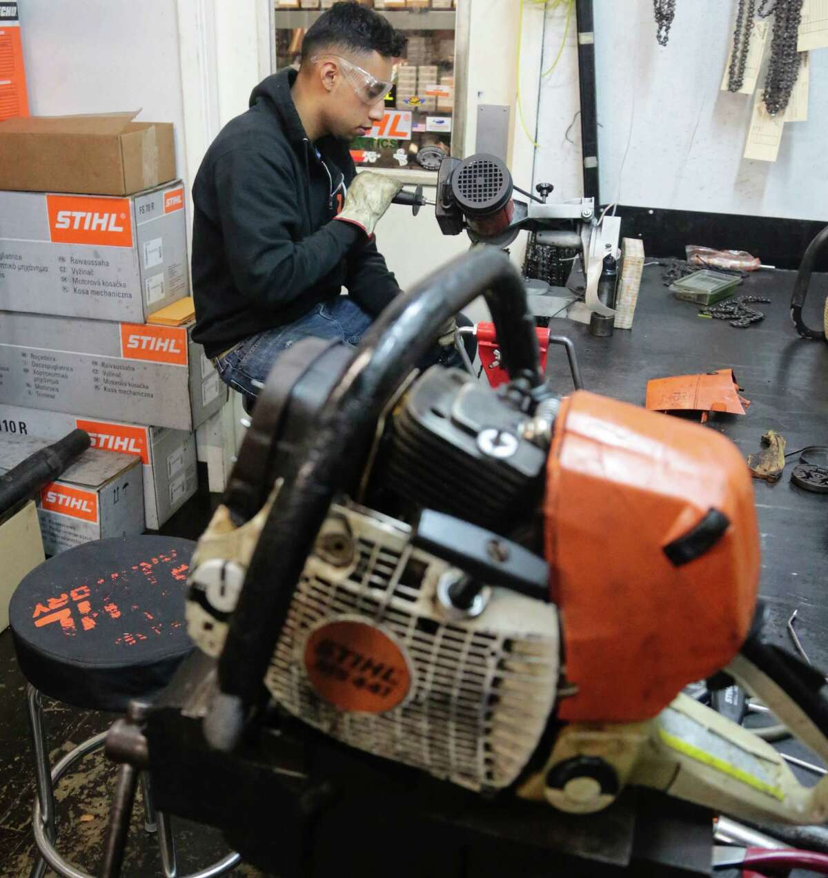 Geovanny Mata sharpens blades on a chain saw. The Cantu brothers like to mentor young people.