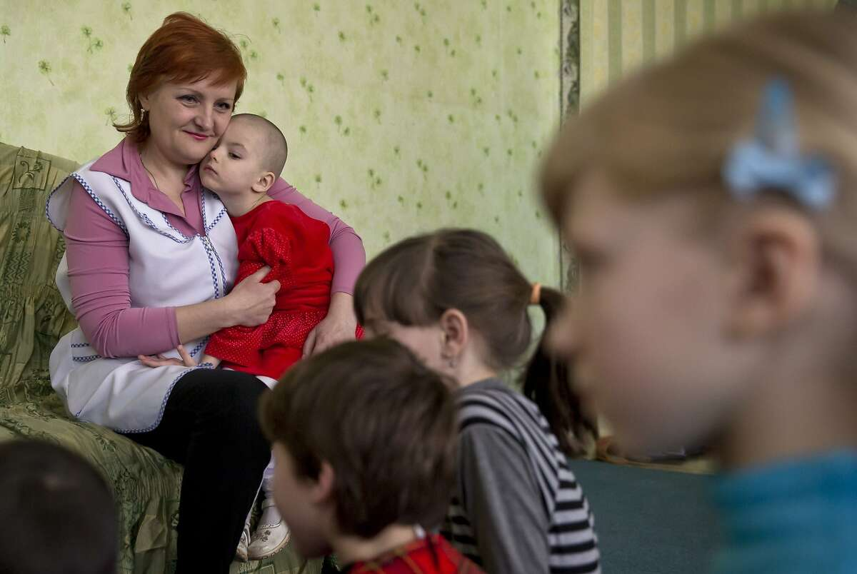 CORRECTS NAME TO LYUBA, INSTEAD OF VERONICA - In a picture taken on Saturday, March 7, 2015, Lyuba presses her cheek against the face of Yelena Nikulenko, director of the children's home in Khartsyzk, Ukraine. A brutal conflict between Russia-backed rebels and Ukrainian government troops has affected more than 1.7 million children on both sides of the front line, according to the UN's children's agency, with some of them sent to orphanages when their parents got killed or went to fight for the rebels, while some parents gave up their foster children because they were no longer receiving benefits for them. (AP Photo/Vadim Ghirda)