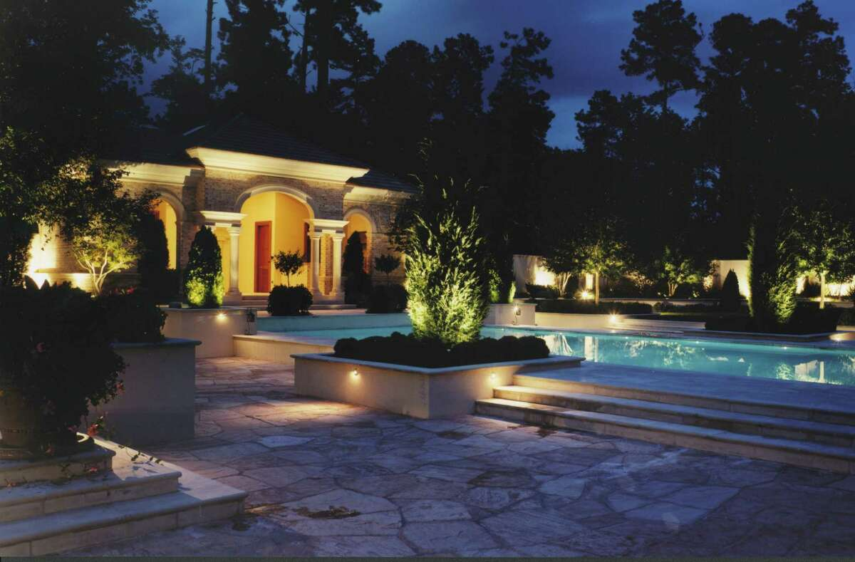 Accent lights brighten a pool and landscape.
