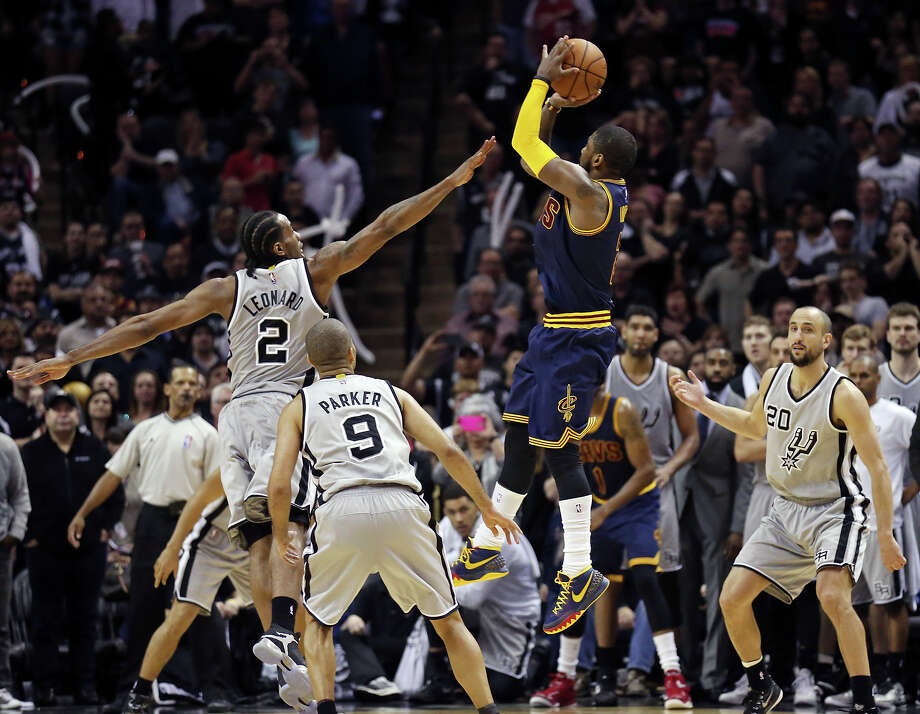 Cavaliers' Kyrie Irving shoots a 3-pointer over the Spurs' Kawhi Leonard as Tony Parker and Manu Ginobili look on late in second half action to send the game to overtime on March 12, 2015 at the AT&T Center. Photo: Edward A. Ornelas /San Antonio Express-News / © 2015 San Antonio Express-News