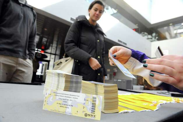 UAlbany cheer team member Madison Corbeil, right, hands America East Championship tickets to students on Thursday March 12, 2015 in Albany, N.Y. UAlbany students with identification where eligible for one ticket to both the women's and men's games. (Michael P. Farrell/Times Union) Photo: Michael P. Farrell / 00030997A