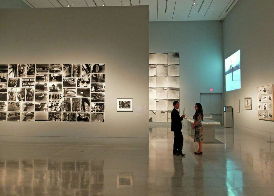 "Yasufumi Nakamori, associate curator of photography, and Allison Pappas, curatorial assistant, stand in one of the large Beck Building galleries at the Museum of Fine Arts, Houston where ""A New World to Come"" is on view through July 12. Photo: Molly Glentzer"