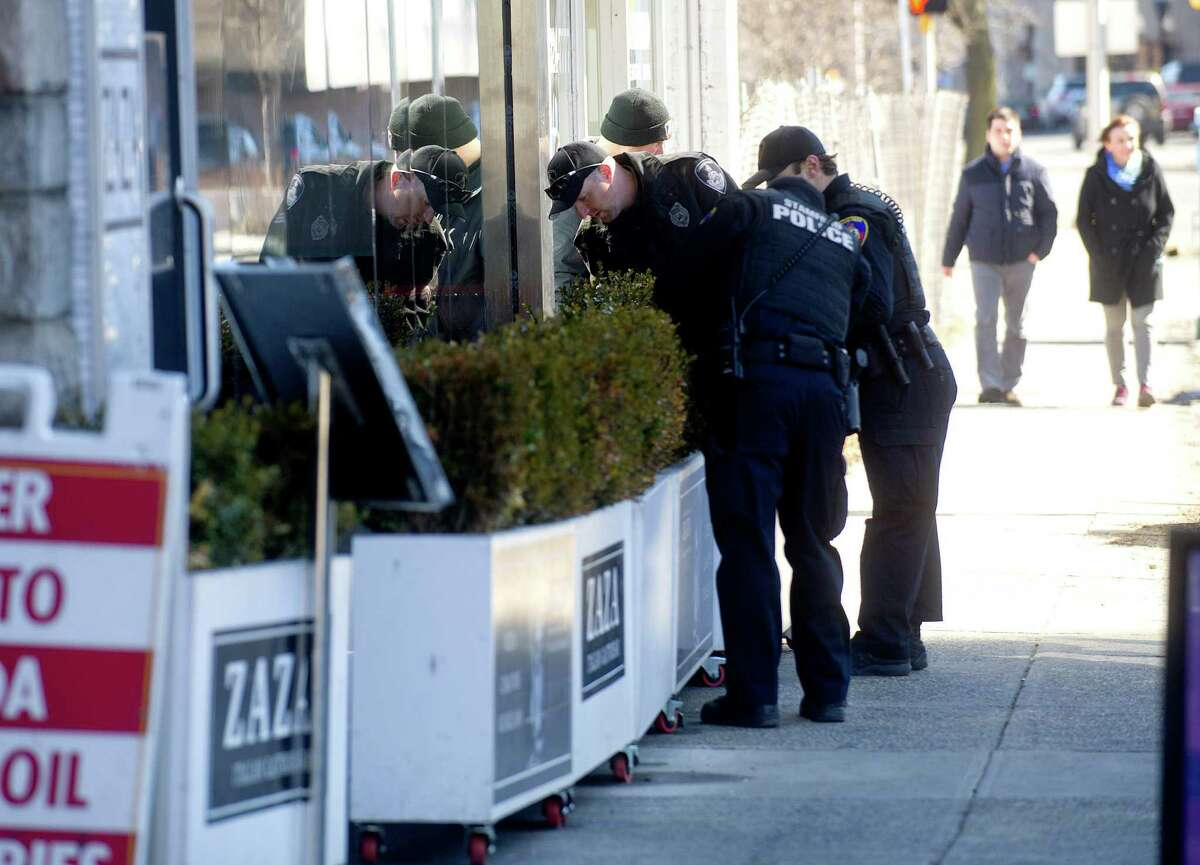 Stamford police officers search the shurbs outside ZAZA Gastrobar in Stamford, Conn., on Thursday, March 12, 2015, after Antonio Muralles was murdered after he was stabbed, beaten and robbed Wednesday night.