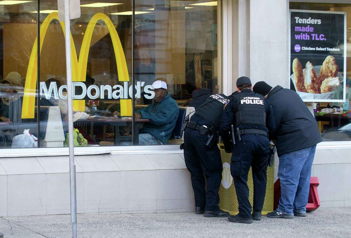 Stamford police officers search the trash bin outside McDonald's in Stamford, Conn., on Thursday, March 12, 2015, after Antonio Muralles was murdered after he was stabbed, beaten and robbed Wednesday night.