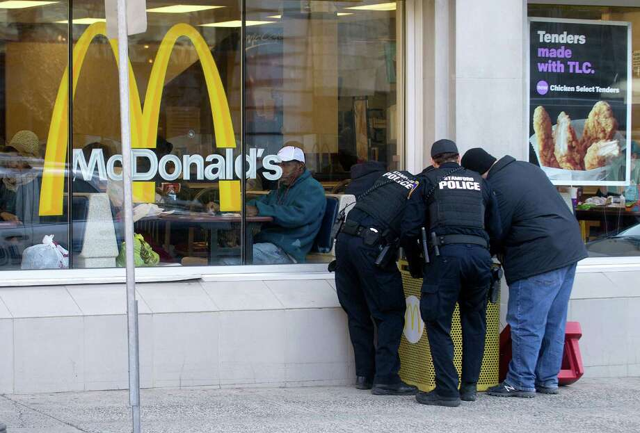 Stamford police officers search the trash bin outside McDonald's in Stamford, Conn., on Thursday, March 12, 2015, after Antonio Muralles was murdered after he was stabbed, beaten and robbed Wednesday night. Photo: Lindsay Perry / Stamford Advocate
