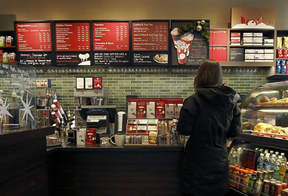 FILE - In this Dec. 5, 2012 file photo, a customer places an order at a Starbucks in Chicago. Areas by cash registers are often crowded withlittle extras in partbecause the closer a customer is to an item, the more likely they are to make an impulse buy. (AP Photo/Charles Rex Arbogast, File) Photo: Charles Rex Arbogast, Associated Press