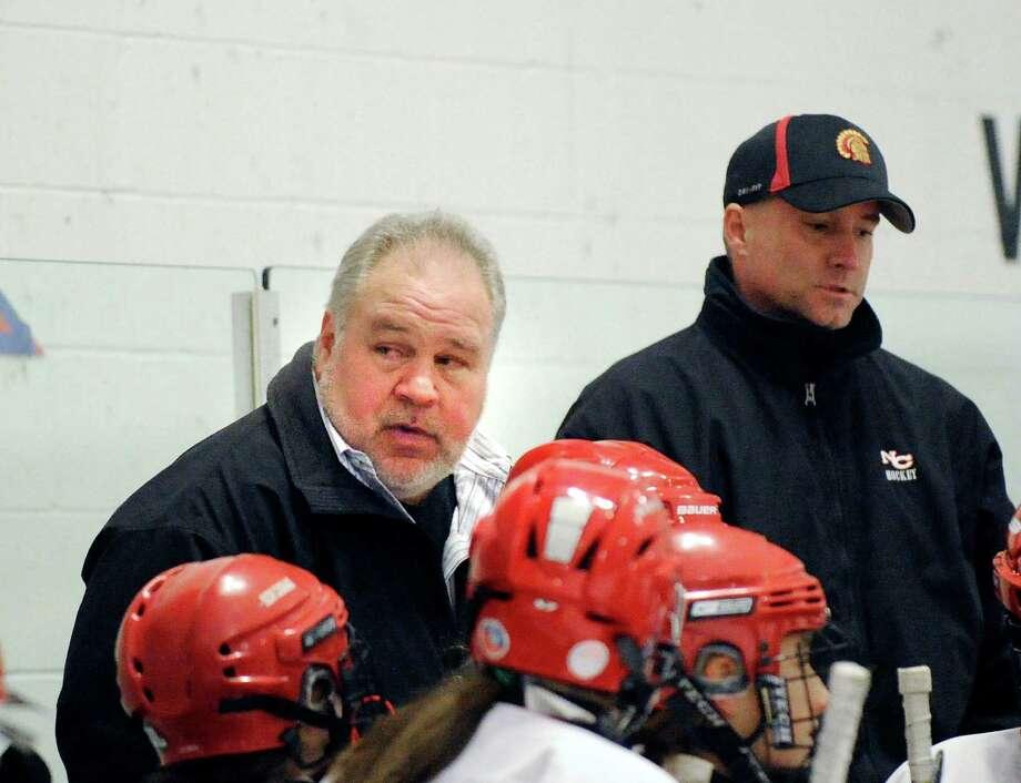 New Canaan High School girls hockey head coach Rich Bulan, left, speaks to his team during game against Greenwich High School, Wednesday night, Dec. 8, 2010. Photo: Bob Luckey, ST / Greenwich Time