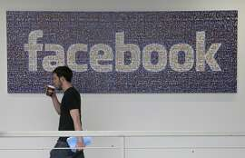 In this March 15, 2013, file photo, a Facebook employee walks past a sign at Facebook headquarters in Menlo Park, Calif. Facebook is giving more options to decide what happens to users' accounts after they die. The world's biggest online social network will now let users pick a trusted contact who can manage their account or elect to have the account deleted, the company announced, Thursday, Feb. 12, 2015. (AP Photo/Jeff Chiu, File)