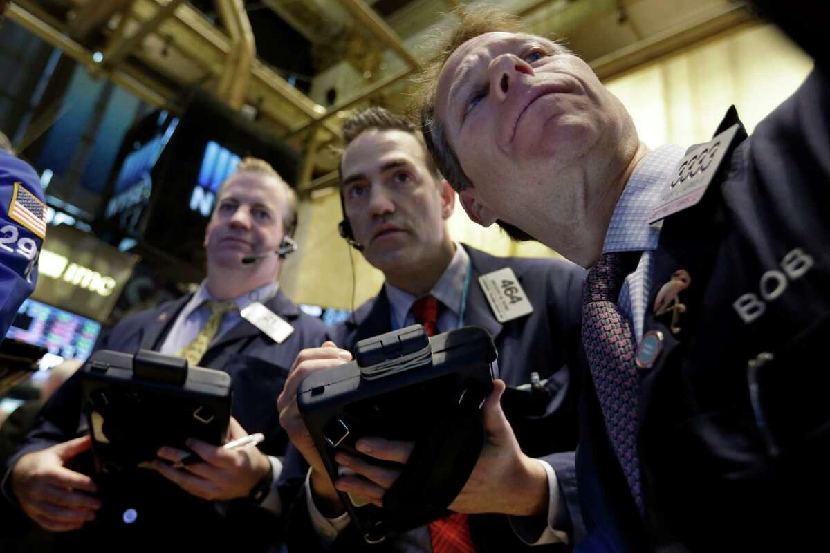 Traders gather at a post on the floor of the New York Stock Exchange. (AP Photo/Richard Drew)