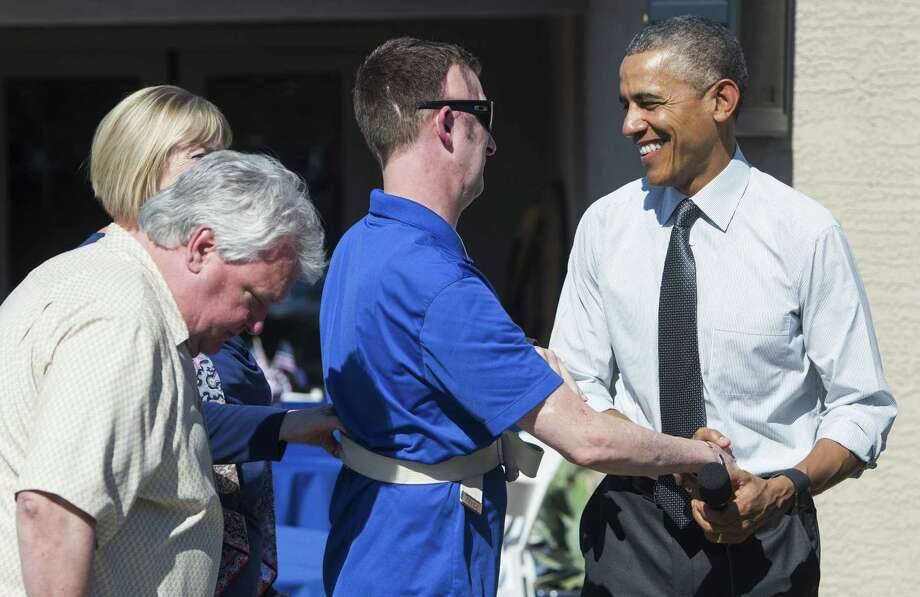 President Barack Obama greets Sgt. 1st Class Cory Remsburg, with his father Craig and stepmother Annie. The sergeant, wounded in Afghanistan, was presented the keys to a new home in Gilbert, Ariz. Photo: SAUL LOEB, Staff / AFP
