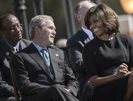Former US President George W. Bush and US First Lady Michelle Obama talk during an event at the Edmund Pettus Bridge on March 7, 2015 in Selma, Alabama. US President Barack Obama and the first family joined others to commemorate the 50th anniversary of Bloody Sunday where voting rights marchers attempting to walk to the Alabama capitol clashed with police at the base of the Edmund Pettus Bridge in Dallas County.    AFP PHOTO/BRENDAN SMIALOWSKIBRENDAN SMIALOWSKI/AFP/Getty Images