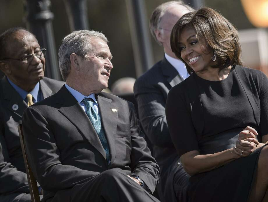 Ex-President George W. Bush and first lady Mich elle Obama talk during an event in Selma, Ala. Photo: Brendan Smialowski, AFP / Getty Images