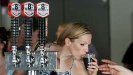 Laura O'Connor samples a brew at the 8th Wonder Brewery in Houston.