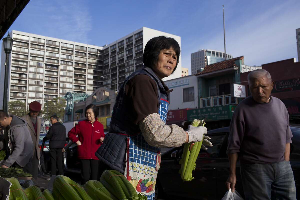 A market worker processes celery in Chinatown in Oakland, Calif. on Friday, March 13, 2015. Oakland?•s new minimum wage law has generated confusion for immigrant businesses in Chinatown, several of which have already shut down because they can?•t afford to pay employees the new rate of $12.25 per hour.