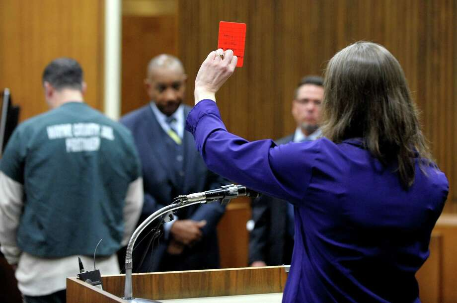 The victim's widow, Kris Bieniewicz, gives the last impact statement and holds up a red card, the signal for ejection in soccer, in a Detroit courtroom on Friday. Photo: Todd McInturf, MBO / Detroit News