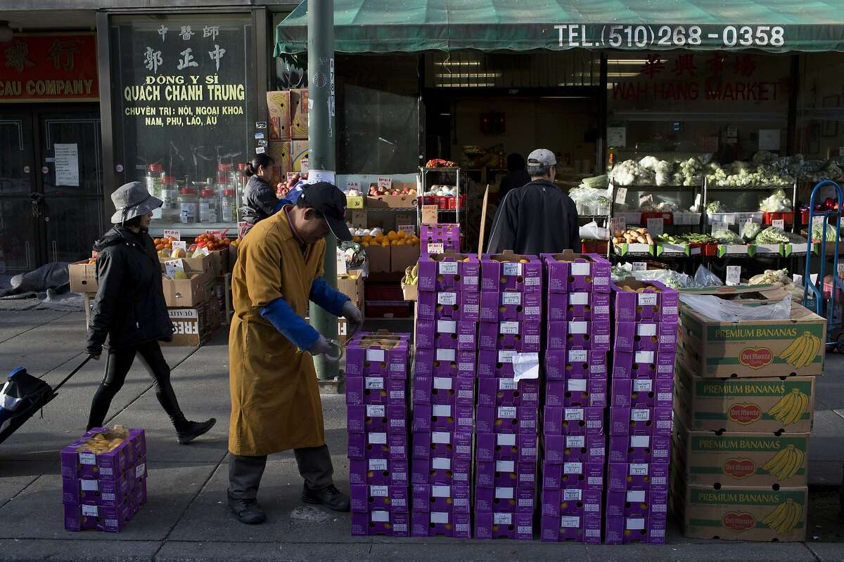 People shop at a market in Chinatown in Oakland on Friday, March 13, 2015.