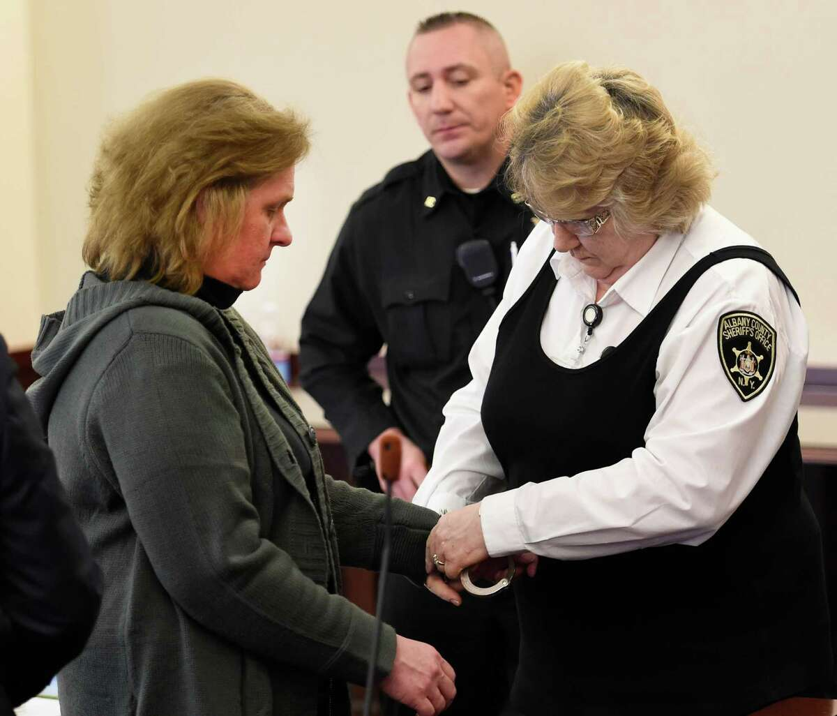 Christina Yerry, left, is handcuffed after receiving the verdict of 2 to 6 years in prison from Judge Roger McDonough at the Judicial Center Friday morning, March 13, 2015, in Albany, N.Y. She was sentenced to state prison Friday for stealing more than $200,000 from a 72-year-old neighbor in Watervliet. (Skip Dickstein/Times Union)