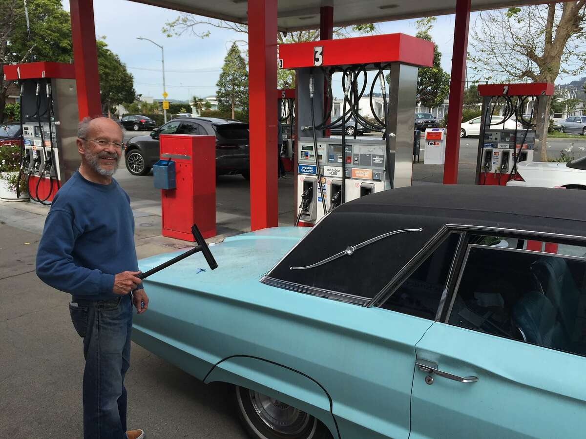 Paul Leclerc, a 68-year-old Sausalito poet, washes the windows of his 1965 Thunderbird after paying $4.97 a gallon for gas at Bridgeway Gas~~