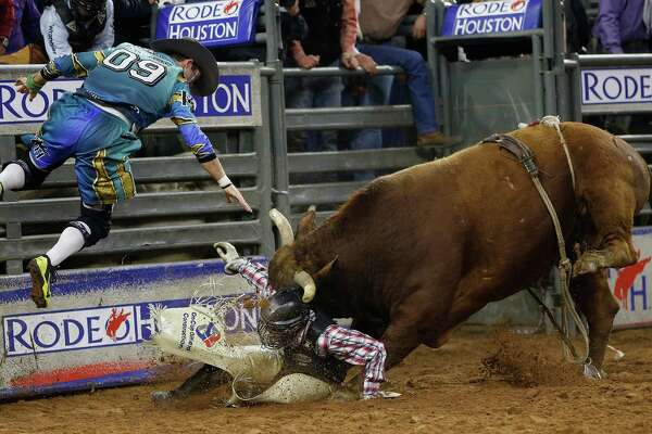 "Bullfighter Dusty Tuckness is tossed up by ""Hangover"" the bull as Tuckness tries to protect Brennon Eldred after he was bucked off during the bull riding competion during the Houston Livestock Show and Rodeo at NRG Stadium, Friday, March 13, 2015, in Houston."