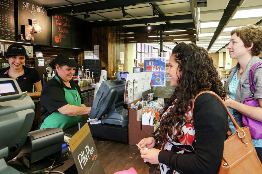 "Staff facualty members Kim Kennedy (from right) and Kristen Cadena purchase coffee from cashier Margaret Contreras and Barista Ashley Shearer at the St. Mary's University Starbucks in the Louis J. Blume Library on Tuesday, March 11, 2015.  St. Mary's University is working to become the first ""fair trade"" campus in Texas.  They are currently promoting their ""Fair Trade Italian Roast Coffee"" advertied on the board above Contreras.  MARVIN PFEIFFER/ mpfeiffer@express-news.net Photo: Marvin Pfeiffer, Staff / San Antonio Express-News / Express-News 2015"