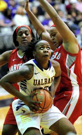UAlbany's Imani Tate, center, looks to the hoop as Hartford's La'Trice Hall, left, and Cherelle Moore defend during their America East Championship game on Friday, March 13, 2015, at UAlbany in Albany, N.Y. (Cindy Schultz / Times Union) Photo: Cindy Schultz / 00030992A