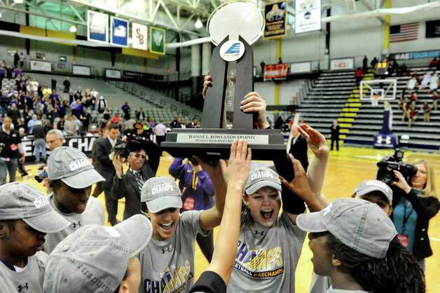 UAlbany's Sarah Royals, center, lifts the trophy and celebrates her team's 84-75 win over Hartford in their America East Championship game on Friday, March 13, 2015, at UAlbany in Albany, N.Y. (Cindy Schultz / Times Union) Photo: Cindy Schultz / 00030992A