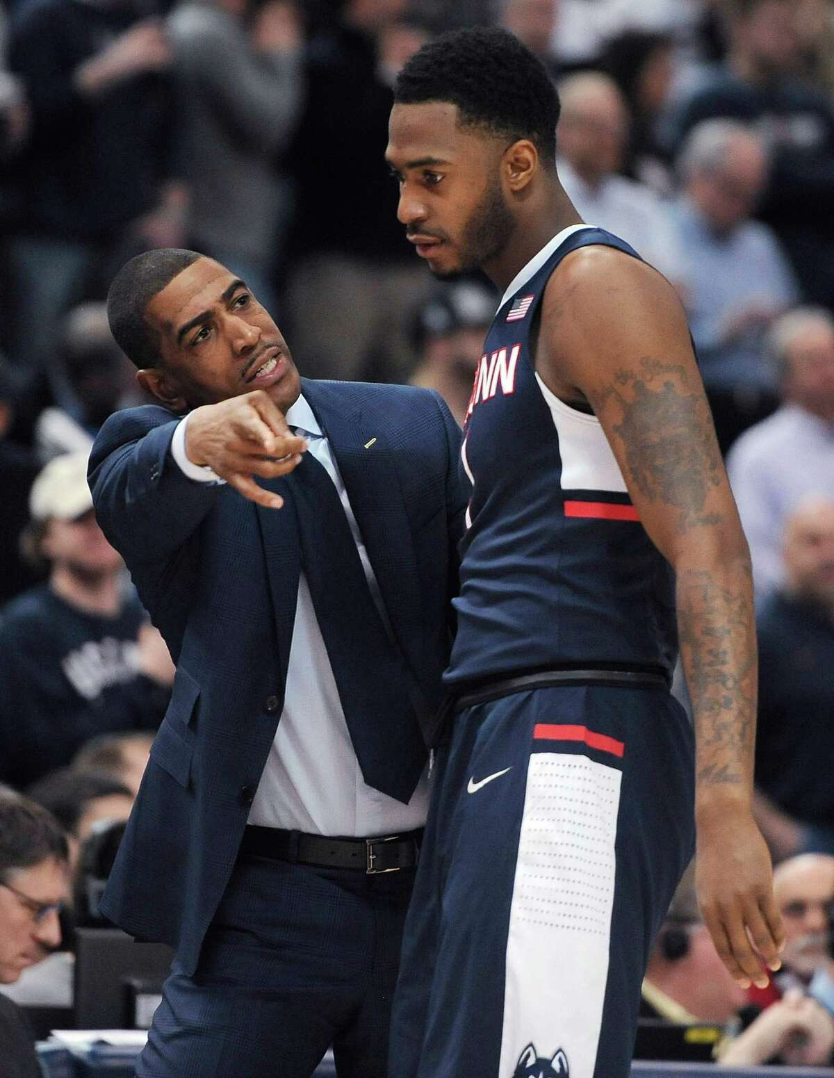 Connecticut coach Kevin Ollie talks with Phillip Nolan during the first half of an NCAA college basketball game against Cincinnati in the quarterfinals of the American Athletic Conference tournament, Friday, March 13, 2015, in Hartford, Conn.