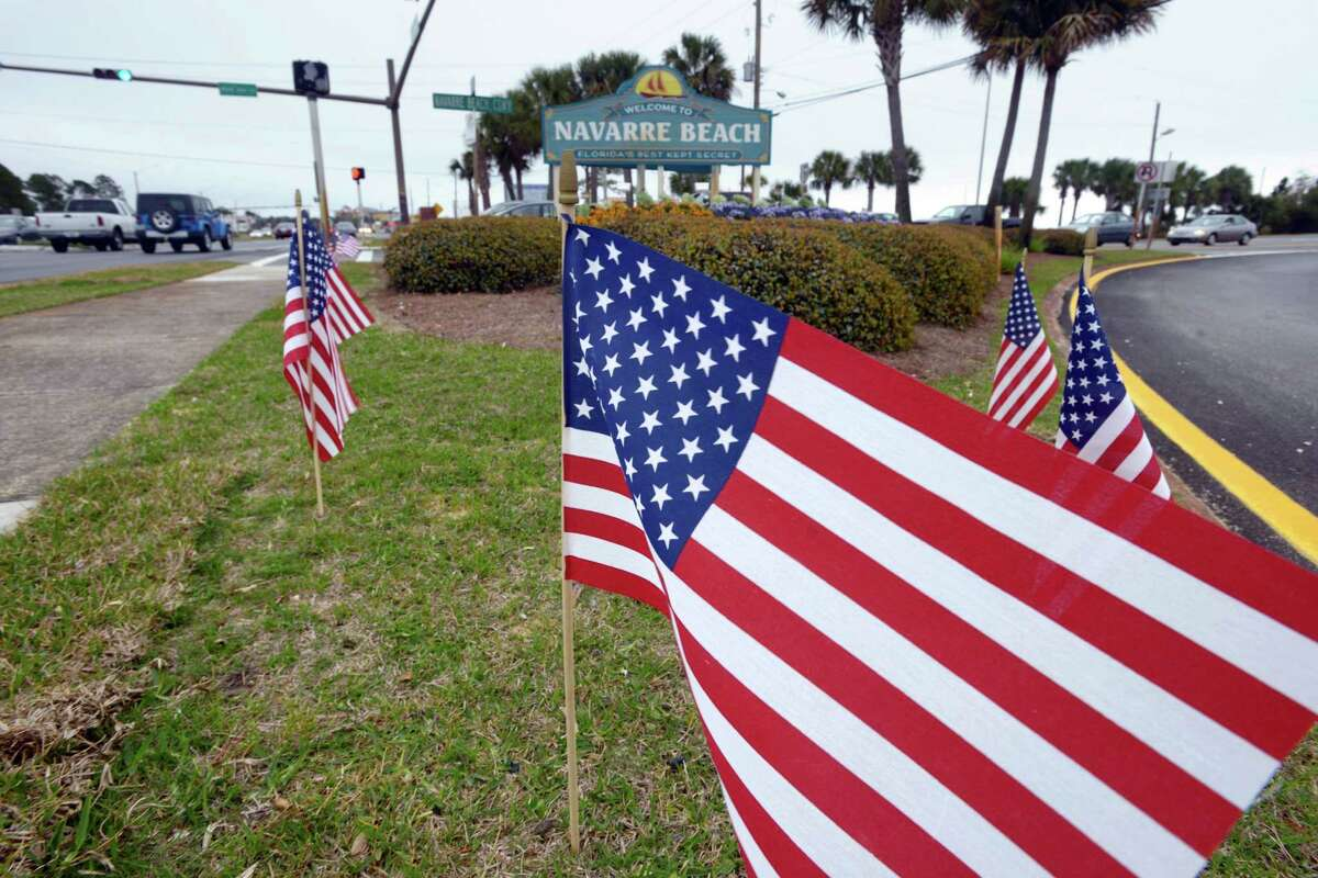 American flags stand in the median near the bridge entrance to Navarre Beach, Fla., Thursday, March 12, 2015. There's been an outpouring of support in this heavily military community following the crash of an Army Black Hawk helicopter Tuesday evening. In various parts of Navarre, 11 flags are placed, one one for each of the servicemen missing in the crash. (AP Photo/Northwest Florida Daily News, Devon Ravine) ORG XMIT: FLPLA104