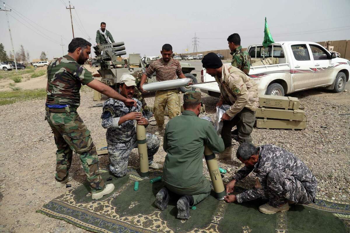 Members of an Iraqi Shiite militant group called Soldiers of Imam Ali Brigades prepare to launch rockets against Islamic State extremists' positions in Qadisiyya neighborhood in Tikrit, 80 miles (130 kilometers) north of Baghdad, Iraq, Friday, March 13, 2015. Iraqi forces entered Tikrit for the first time on Wednesday from the north and south. On Friday, they fought fierce battles to secure the northern Tikrit neighborhood of Qadisiyya and lobbed mortars and rockets into the city center, still in the hands of IS. Iraqi military officials have said they expect to reach the center of Tikrit within two to three days. (AP Photo/Khalid Mohammed) ORG XMIT: BKM105