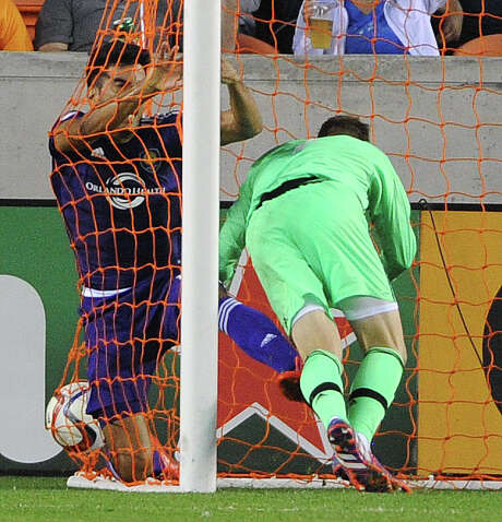 Orlando City SC midfielder Pedro Ribeiro, left, and Dynamo goalkeeper Tyler Deric fall into the net after Deric's own-goal in the 74th minute. Photo: Eric Christian Smith, Freelance / 2015 Eric Christian Smith