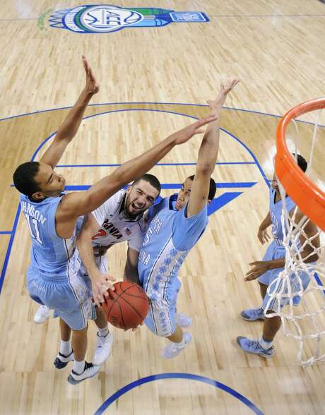 Virginia's London Perrantes finds his path to the basket blocked by the defensive pressure of North Carolina's Brice Johnson, left, and Marcus Paige, right. Photo: Grant Halverson, Stringer / 2015 Getty Images