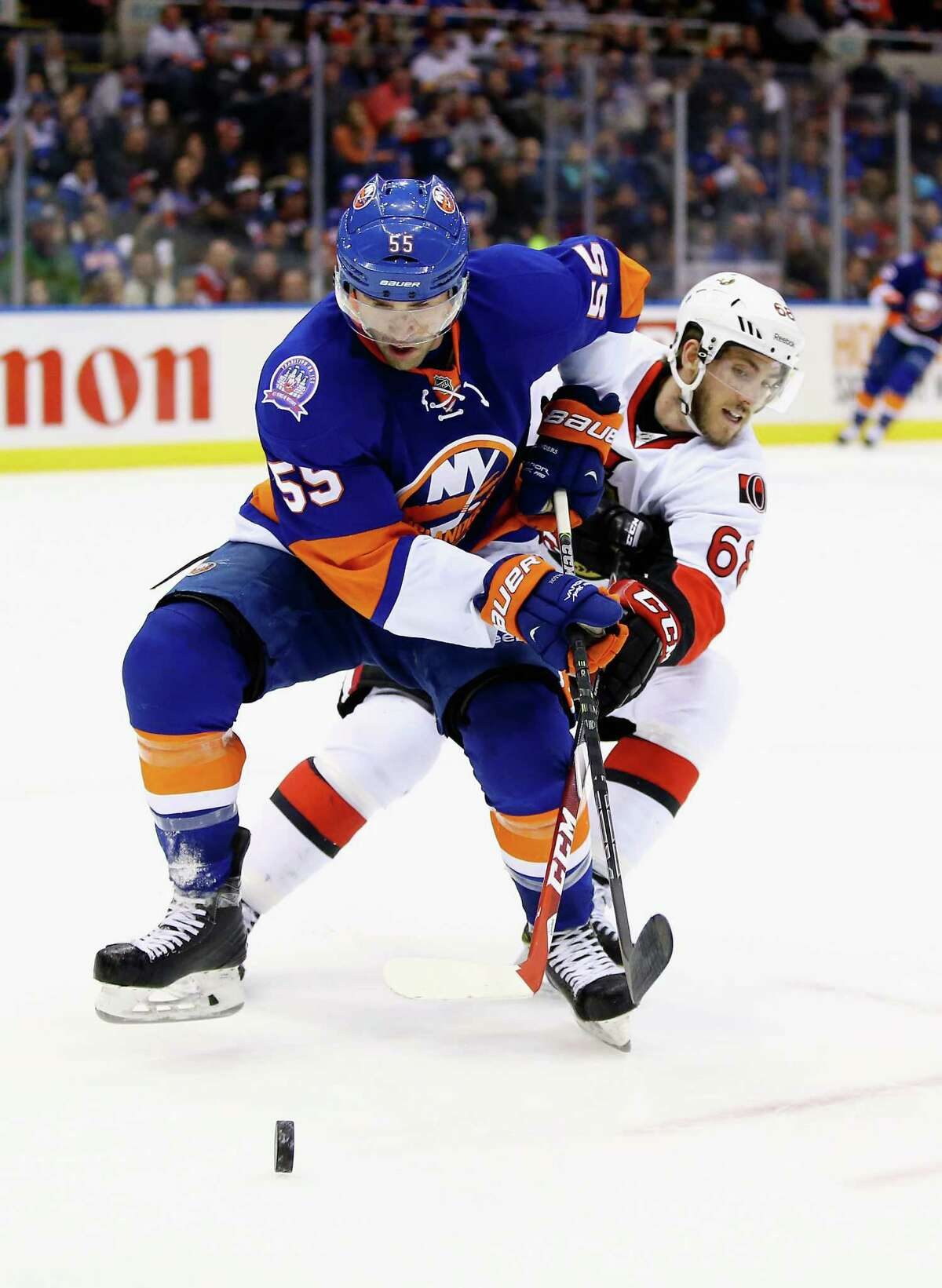 UNIONDALE, NY - MARCH 13: Johnny Boychuk #55 of the New York Islanders and Mike Hoffman #68 of the Ottawa Senators battle for the puck during their game at the Nassau Veterans Memorial Coliseum on March 13, 2015 in Uniondale, New York. (Photo by Al Bello/Getty Images) ORG XMIT: 507050803