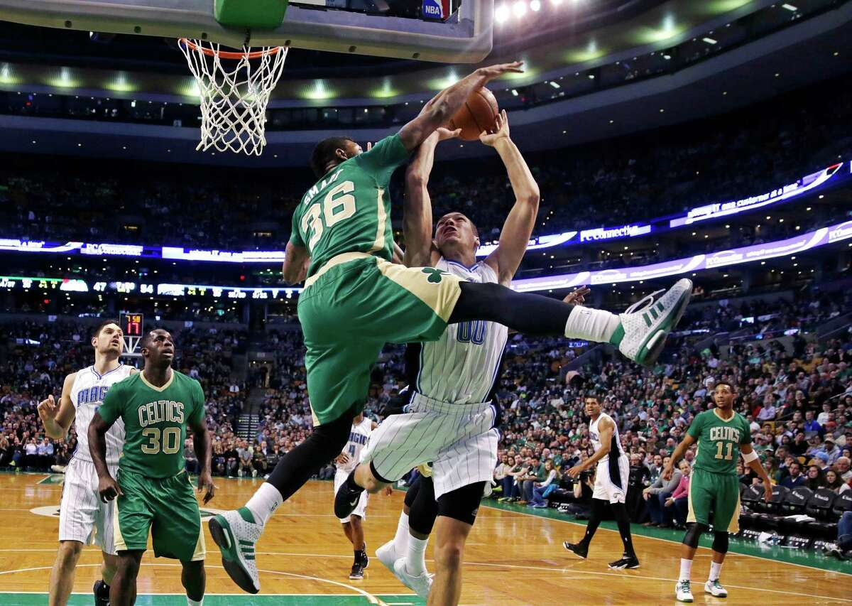 Boston Celtics guard Marcus Smart (36) blocks Orlando Magic forward Aaron Gordon (00) on a drive to the basket during the second half of an NBA basketball game in Boston, Friday, March 13, 2015. The Celtics defeated the Magic 95-88. (AP Photo/Charles Krupa) ORG XMIT: MACK106