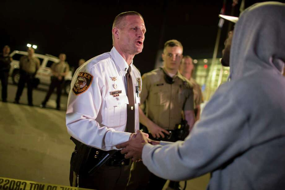 St. Louis County police Lt. Jerry Lohr talks with a protester outside the police department in Ferguson, Mo. Photo: Whitney Curtis /New York Times / NYTNS