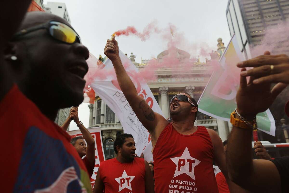Demonstrators wearing Workers Party t-shirts hold flares and shout slogans during a protest in support of the state-run oil company Petrobras in Rio de Janeiro, Brazil, Friday, March 13, 2015. Brazilian unions and backers of President Dilma Rousseff marched Friday in several cities across the nation, mostly to show support for state-run oil company Petrobras as it's engulfed by a corruption scandal, but also to back Rousseff.