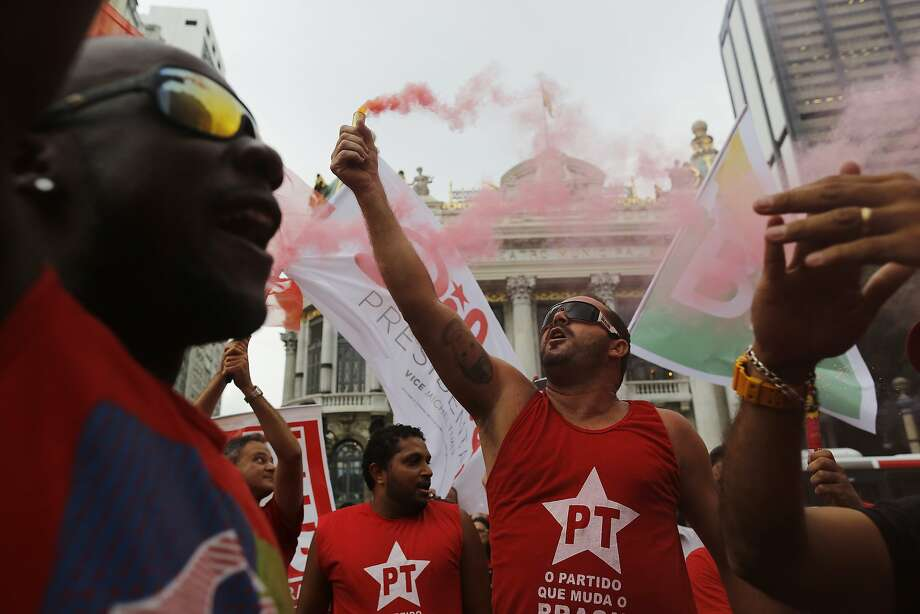 Demonstrators wearing Workers Party t-shirts hold flares and shout slogans during a protest in support of the state-run oil company Petrobras in Rio de Janeiro, Brazil, Friday, March 13, 2015. Brazilian unions and backers of President Dilma Rousseff marched Friday in several cities across the nation, mostly to show support for state-run oil company Petrobras as it's engulfed by a corruption scandal, but also to back Rousseff. Photo: Leo Correa, Associated Press