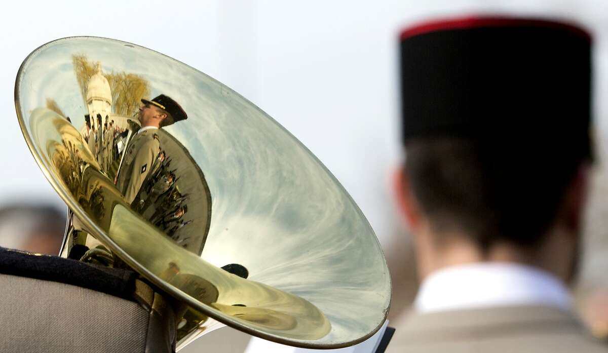 The reflection of a French soldier and the Neuve Chapelle Indian Monument is reflected in the bell of a musical instrument during a WWI commemoration ceremony at the Neuve Chapelle Indian Memorial in Neuve Chapelle, France on Friday, March 13, 2015. The Memorial commemorates over 4,700 Indian soldiers and workers who lost their lives on the Western Front during WWI and have no known grave.