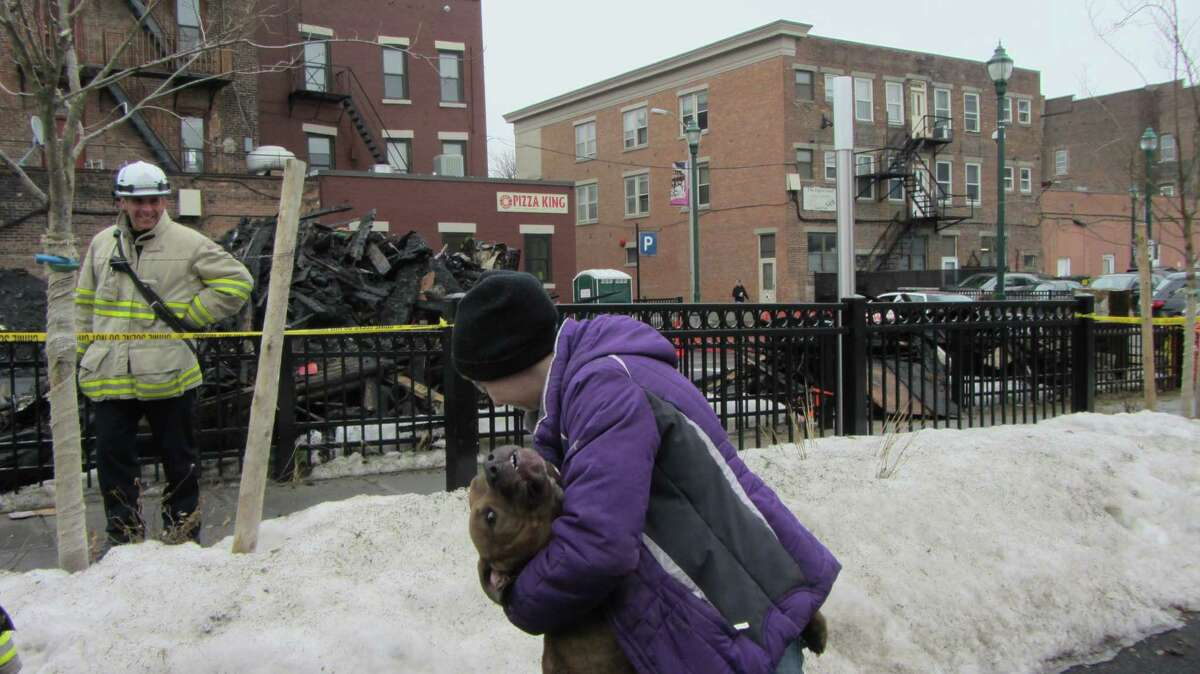 Staci Lydon is reunited with her dog, Zeus, on Saturday, March 14, eight days after fire tore through the apartment building on Jay Street in Schenecady where it was staying with her friend. (Bob Gardinier/Times Union)