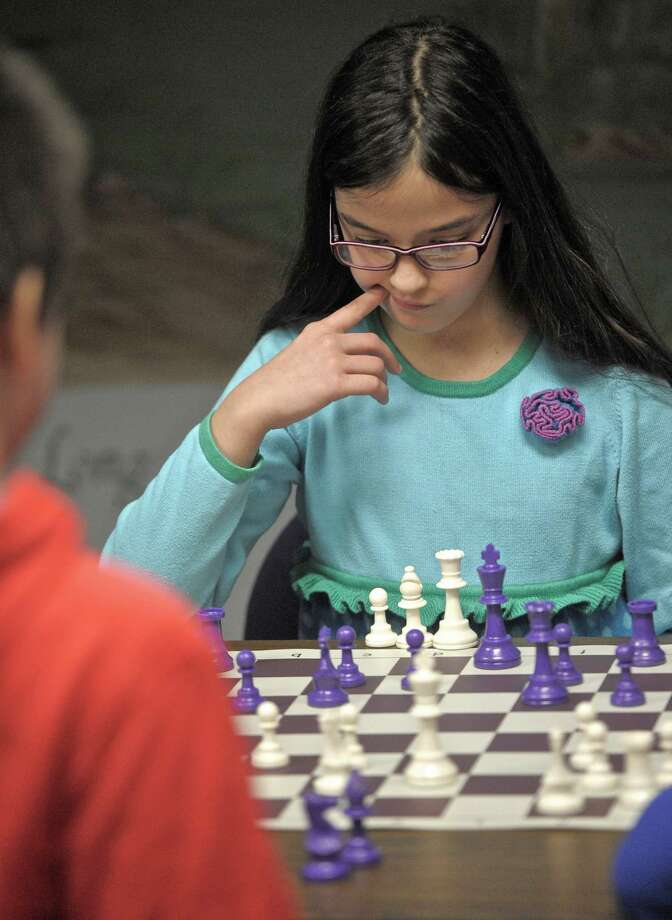 Andalucia Rodriguez, 10, of Newtown, ponders her next move while competing in the 53rd Connecticut Association of Schools Scholastic Chess Championship, held at the  Cyenius H. Booth Library, in Newtown, Conn, on Saturday, March 14, 2015. Over 50 students competed in the tournament, ranging in age from kindergarten to high school, which was held for the first time in western Connecticut. Each student played 4 games, being matched in thei next game by their scores from the previous game. Photo: H John Voorhees III / The News-Times